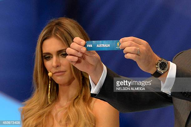 Secretary General Jerome Valcke shows the paper with the name of Australia as Brazilian presenter Fernanda Lima looks on during the final draw of the...