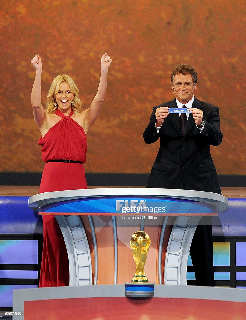 Secretary General Jérôme Valcke holds the name of South Africa as Charlize Theron cheers during the Final Draw for the FIFA World Cup 2010 December 4, 2009 at the International Convention Centre in Cape Town, South Africa.