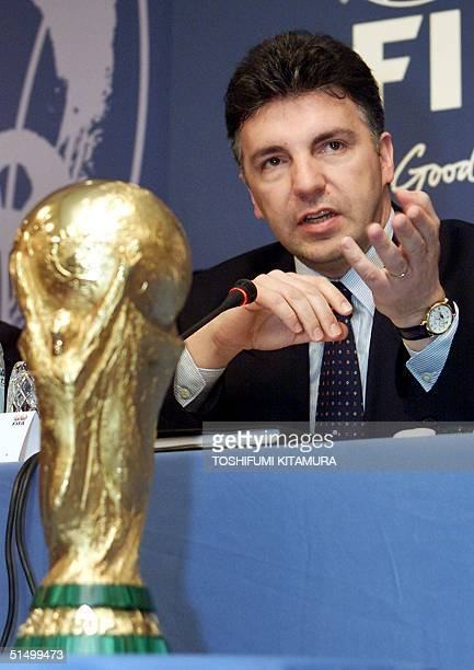 Secretary General Michel ZenRuffinen answers a question behind a replica of the World Cup trophy during a press conference following the 2002 FIFA...