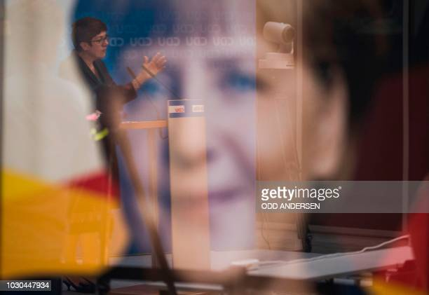 Secretary General of the Christian Democratic Union Annegret KrampKarrenbauer is reflected in the glass of a poster of German Chancellor Angela...