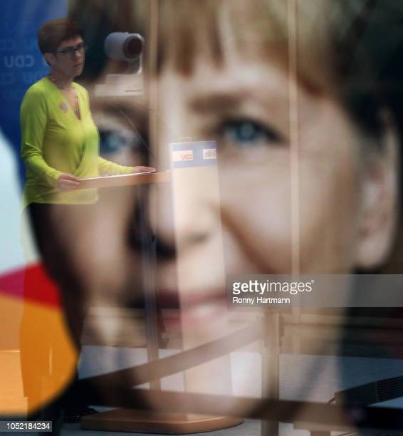 Secretary General of the Christian Democratic Union Annegret KrampKarrenbauer is reflected in a picture of German Chancellor Angela Merkel after a...