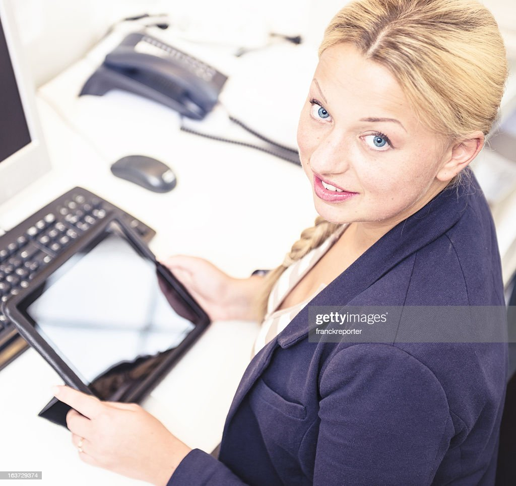 Secretary in her office using a digital tablet : Stock Photo