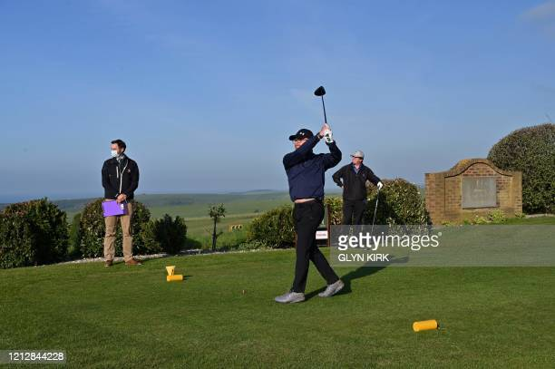 Secretary Martin Yeates watches member David Scales tee off from the 1st at The Dyke Golf Club on the south coast of England on May 13 as the golf...