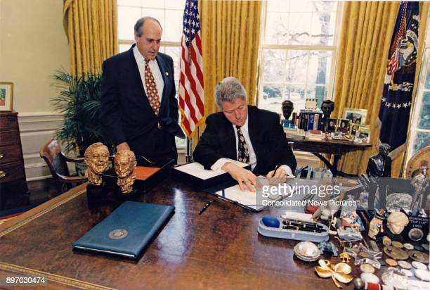 US Secretary of Agriculture Dan Glickman watches as US President Bill Clinton signs HR 2854 in the White House's Oval Office Washington DC April 4...