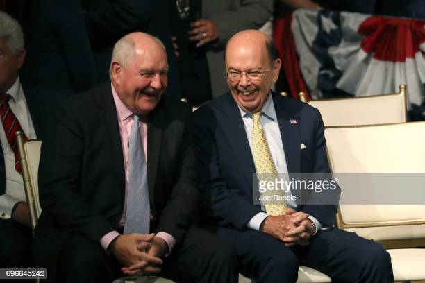 Secretary of Agriculture Sonny Perdue and Secretary of Commerce Wilbur Ross wait for US President Donald Trump to speak about policy changes he is...