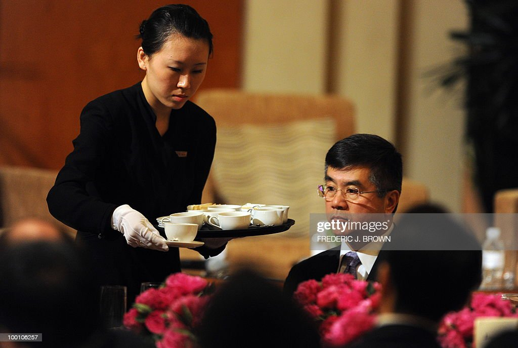 US Secretary of Commerce Gary Locke looks on as a waitress serves coffee ahead of his speech at a business luncheon in Beijing on May 21, 2010. Locke is on the final stop of a three-city visit to China which earlier included Hong Kong and Shanghai, leading the first cabinet-level US trade mission since the US announced an ambitious target in March to double US shipments within five years to promote job growth. AFP PHOTO/Frederic J. BROWN