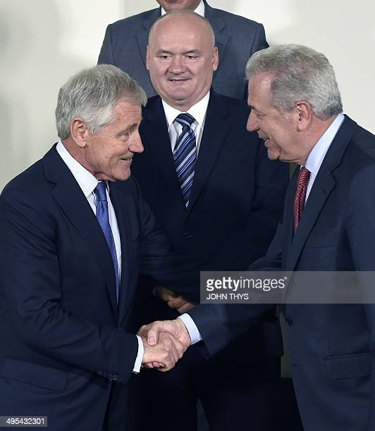 US Secretary of Defence Chuck Hagel shakes hands with his Greek counterpart Dimitrios Avramopoulos as the defence minster of Hungary Csaba Hende...