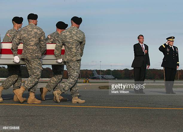 Secretary of Defense Ash Carter stands at attention with US Army Chief of Staff Gen Mark Milley while a US Army carry team moves the transfer case of...