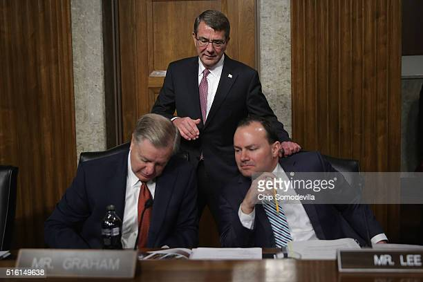 S Secretary of Defense Ashton Carter tries to get the attention of Senate Armed Services Committee members Sen Lindsey Graham and Sen Mike Lee before...