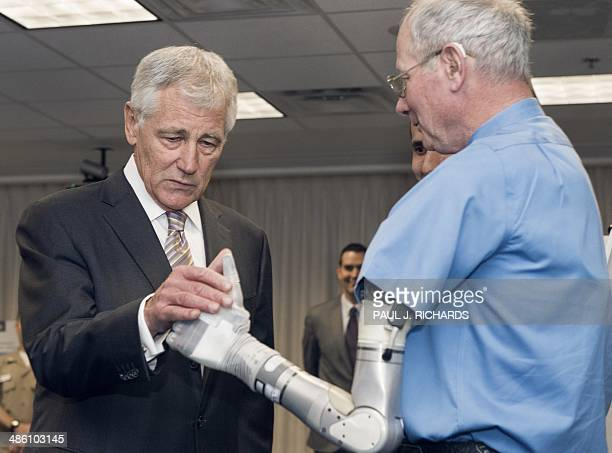 US Secretary of Defense Chuck Hagel greets an old friend Fred Downs Jr who lost an arm in a landmine explosion while fighting in Vietnam and now...