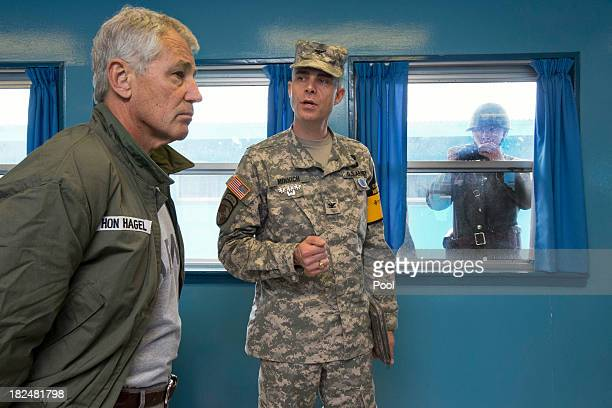 S Secretary of Defense Chuck Hagel left listens to US Army Col James Minnich as a North Korean soldier takes a photograph of the secretary through a...