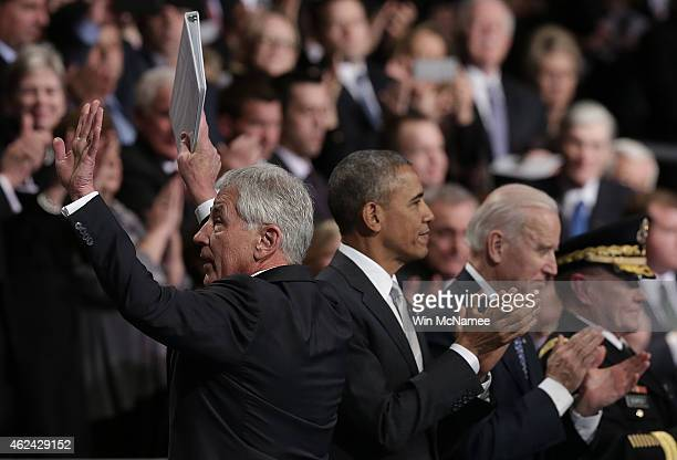 US Secretary of Defense Chuck Hagel waves from the reviewing stand alogside US President Barack Obama US Vice President Joe Biden and Chairman of the...