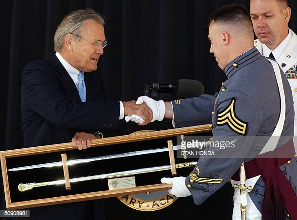Secretary of Defense Donald Rumsfeld accepts the gift of a sword from Cadet John M Zdeb 2004 class president of the US Military Academy 29 May 2004...
