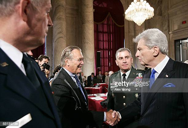 Secretary of Defense Donald Rumsfeld shakes hands with committee chairman Sen John Warner as Commander of US Central Command Gen John Abizaid and...