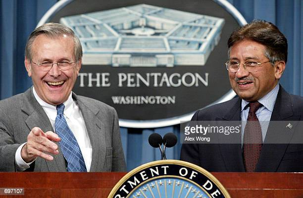 Secretary of Defense Donald Rumsfeld takes questions from reporters as Pakistani President Pervez Musharraf looks on February 13, 2002 during a news...