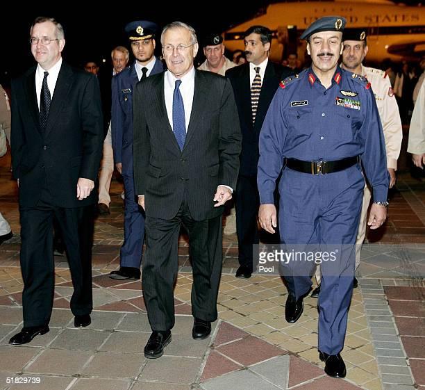 S Secretary of Defense Donald Rumsfeld walks with Chief of Staff of Kuwait Armed Forces LtGen Fahd AlAmir and US Ambassador to Kuwait Richard LeBaron...