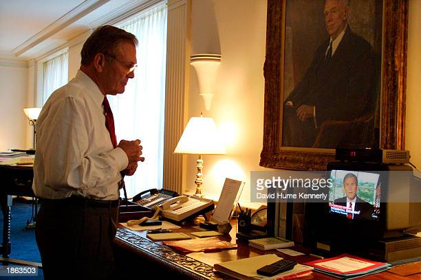 US Secretary of Defense Donald Rumsfeld watches television as President George W Bush announce attacks on terrorists in Afghanistan October 7 2001 in...