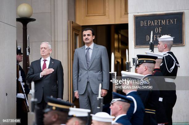 US Secretary of Defense James Mattis and Qatar's Emir Sheikh Tamim Bin Hamad AlThani listen to the US national anthem during an honor cordon at the...