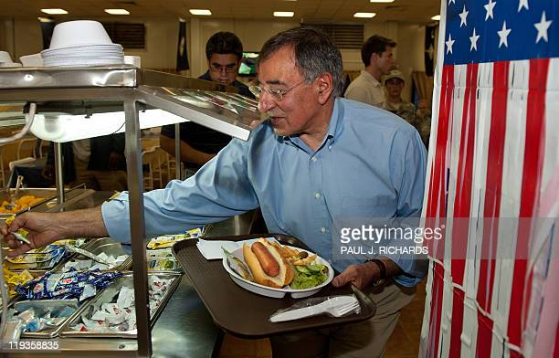 US Secretary of Defense Leon Panetta reaches for a packet of mustard and relish as he takes a hot dog for lunch during his visit to Camp Victory in...