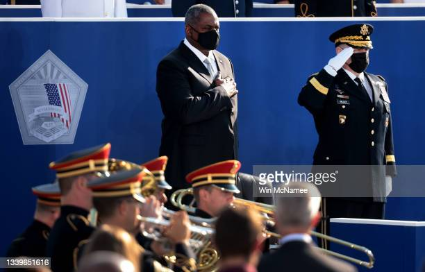 Secretary of Defense Lloyd Austin and Chairman of the Joint Chiefs of Staff Gen. Mark A. Milley stand for the national anthem during the Pentagon...