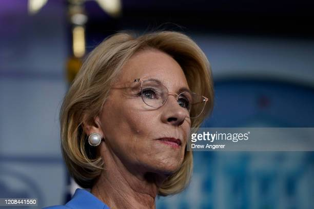 Secretary of Education Betsy DeVos listens as US President Donald Trump speaks during a briefing on the coronavirus pandemic in the press briefing...