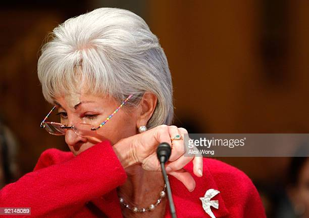 Secretary of Health and Human Services Kathleen Sebelius coughes onto her sleeve during a hearing before the Senate Homeland Security and...