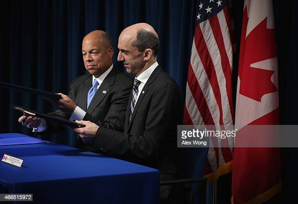 S Secretary of Homeland Security Jeh Johnson exchanges documents with Canadian Minister of Public Safety and Emergency Preparedness Steven Blaney as...