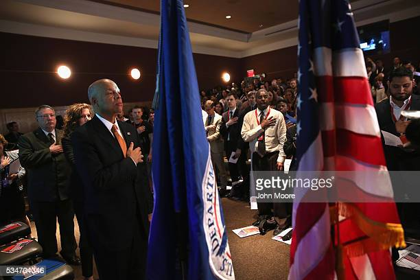 S Secretary of Homeland Security Jeh Johnson stands with immigrants for the pledge of allegiance during a naturalization ceremony for new American...