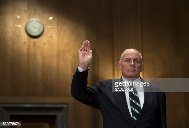 US Secretary of Homeland Security John Kelly is sworn in prior to testifying during a Senate Homeland Security and Governmental Affairs Committee...