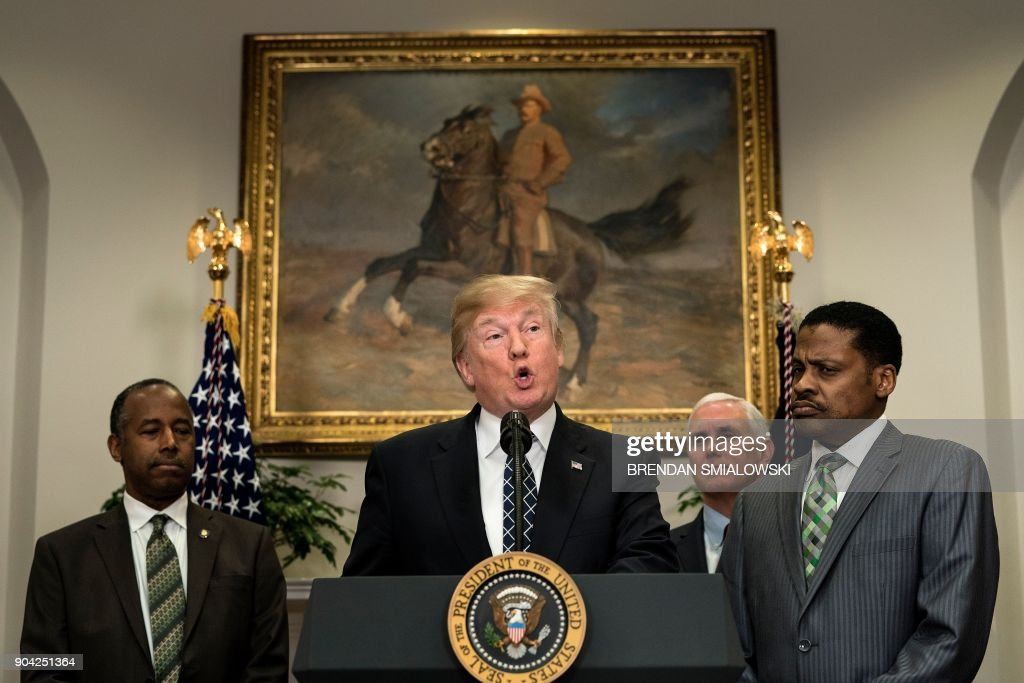 Secretary of Housing and Urban Development Ben Carson (L), US Vice President Mike Pence (2R) and Isaac Newton Farris Jr. (R) listen while US President Donald Trump speaks during an event about Martin Luther King Jr. in the Roosevelt Room of the White House January 12, 2018 in Washington, DC. / AFP PHOTO / Brendan Smialowski