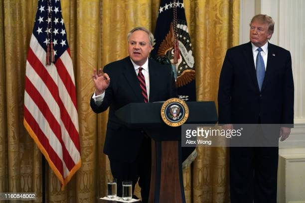 S Secretary of Interior David Bernhardt speaks as President Donald Trump looks on during an East Room event on the environment July 7 2019 at the...