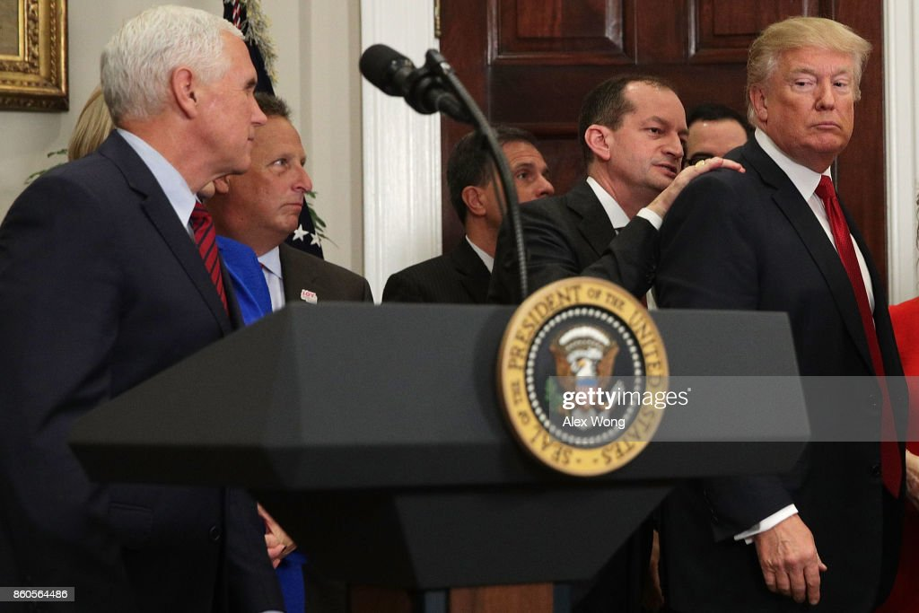 U.S. Secretary of Labor Alexander Acosta (2nd R) taps on the shoulder of U.S. President Donald Trump (R) to remind him to sign an executive order after his remarks as Vice President Mike Pence (L) looks on in the Roosevelt Room of the White House October 12, 2017 in Washington, DC. President Trump signed the executive order to loosen restrictions on Affordable Care Act 'to promote healthcare choice and competition.'