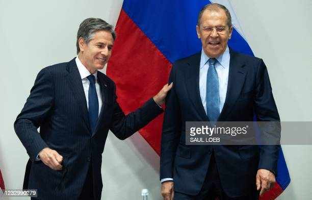 Secretary of State Antony Blinken greets Russian Foreign Minister Sergey Lavrov as they arrive for a meeting at the Harpa Concert Hall in Reykjavik,...
