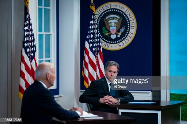 Secretary of State Antony Blinken listens as U.S. President Joe Biden speaks during a conference call on climate change with the Major Economies...