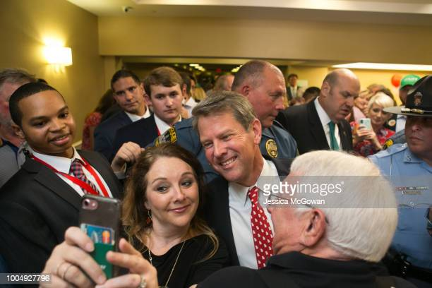 Secretary of State Brian Kemp takes a selfie with supporter Becky Carlan during an election watch party on July 24 2018 in Athens Georgia Kemp...