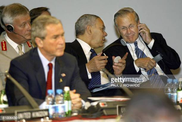 Secretary of State Colin Powell and US Secretary of Defense Donald Rumsfeld sit behind US President George W Bush and discuss business during a...