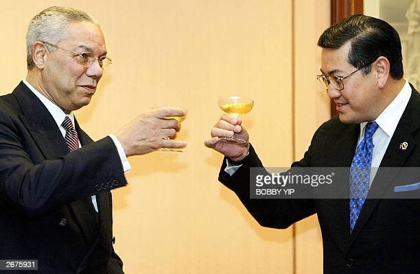 Secretary of State Colin Powell makes a toast with Thai Foreign Minister Surakiart Sathirathai after signing an agreement on air cargo during their...