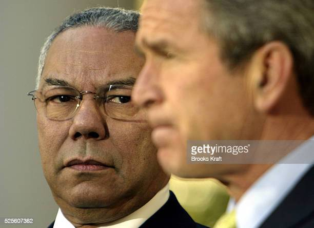 Secretary of State Colin Powell stands with President George W Bush