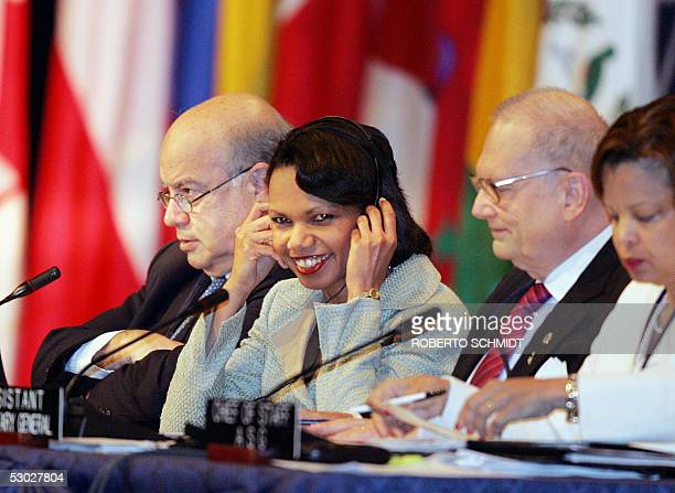 Secretary of State Condoleezza Rice smiles as she listens to a translation using a headphone during the opening of the first Plenary Session of the...