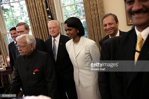 Secretary of State Condoleezza Rice watches as U.S. President George W. Bush greets India's Prime Minister Manmohan Singh in the Oval Office of the...
