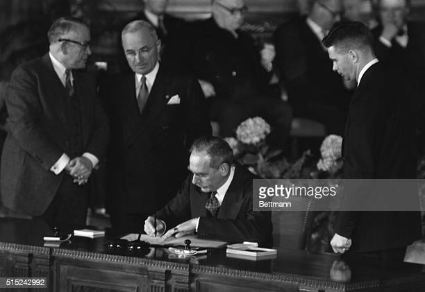 Secretary of State Dean Acheson signs the North Atlantic Treaty in Washington Standing beside him are Vice President Alben W Barkley President Harry...