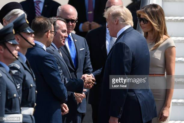 Secretary of State for International Trade Liam Fox greets US President Donald Trump following the President's arrival at Stansted Airport on July 12...