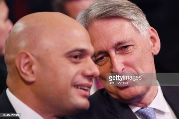 Secretary of State for the Home Department Sajid Javid speaks to Chancellor of the Exchequer Philip Hammond as take their seats ahead of British...