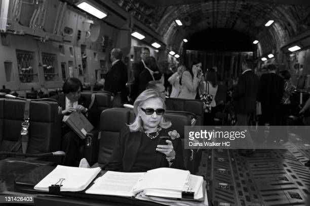 Secretary of State Hillary Clinton aboard a C17 checking her PDA in sunglasses upon departure from Malta bound for a meeting with rebel leaders in...