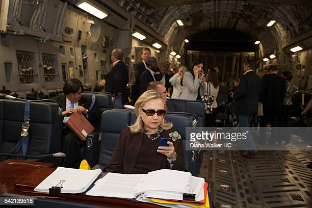 Secretary of State Hillary Clinton, aboard a C-17, checking her PDA in sunglasses upon departure from Malta bound for a meeting with rebel leaders in...