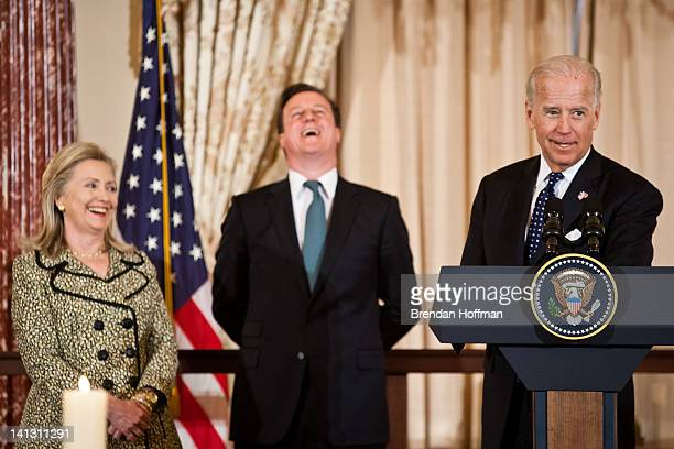 S Secretary of State Hillary Clinton and British Prime Minister David Cameron share a laugh as Vice President Joe Biden gives a toast during a lunch...