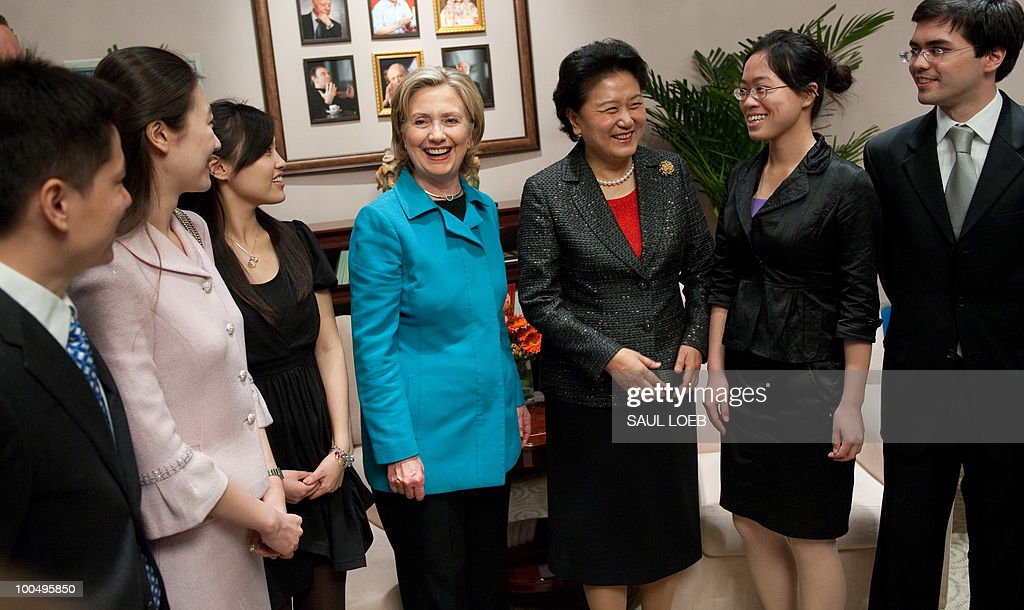 US Secretary of State Hillary Clinton (C) and Chinese State Councilor Liu Yandong (3rd R) greet students during a meeting at the National Center for the Performing Arts in Beijing on May 25, 2010. Clinton arrived in Beijing on May 23 ahead of talks with Chinese leaders on trade issues and security threats including renewed tensions on the Korean peninsula. Clinton flew into the capital from Shanghai, where she had toured the World Expo site, and attended a state dinner hosted by Dai Bingguo, a member of China's State Council, or cabinet. AFP PHOTO / POOL / Saul LOEB