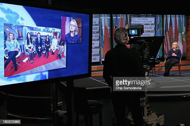 S Secretary of State Hillary Clinton appears on a television screen as she answers questions from youths at the BBC's London offices during a 'Global...