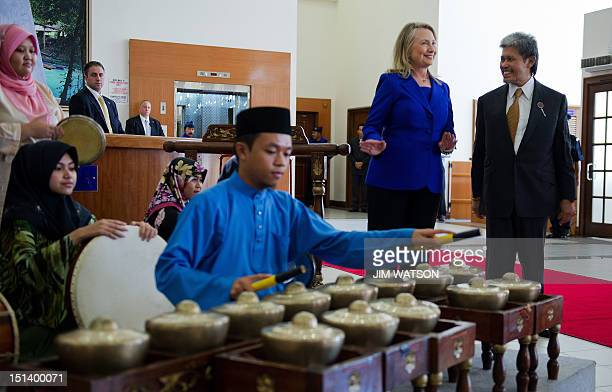 US Secretary of State Hillary Clinton does a little dance with Brunei's Foreign Minister Prince Mohamed Bolkiah as they arrive at Universiti Brunei...