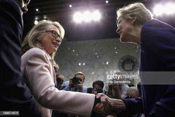 S Secretary of State Hillary Clinton greets Sen Elizabeth Warren as they arrive for Sen John Kerry's confirmation hearing before the Senate Foreign...